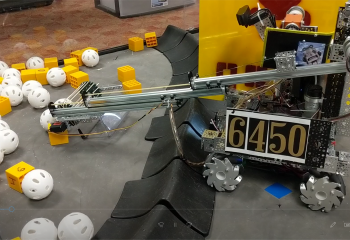 """The Jagbots FTC 6450 Robotics team picks up a """"mineral"""" as part of the """"Rover Ruckus"""" Challenge."""